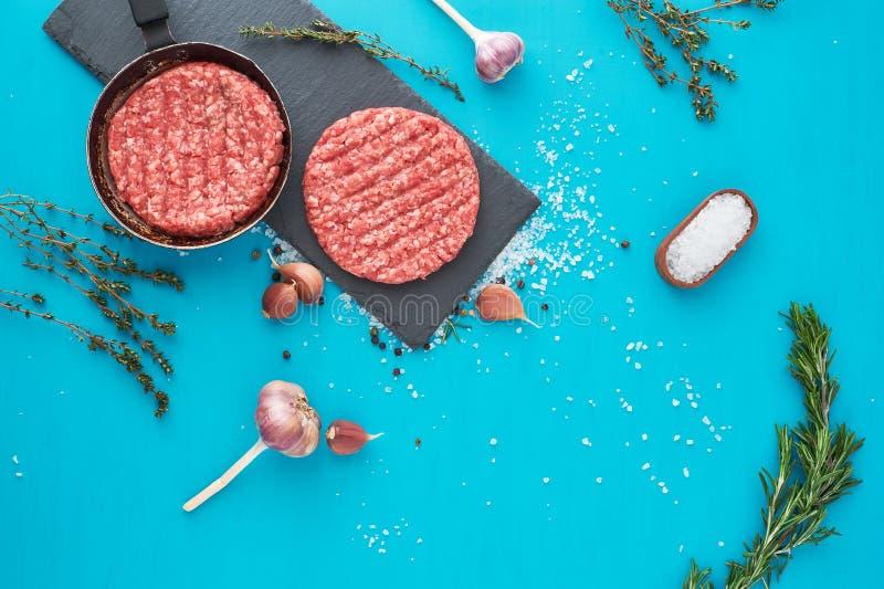 Carne cruda fresca de la carne de vaca con las hierbas y la sal en fondo de la turquesa imagen de archivo libre de regalías