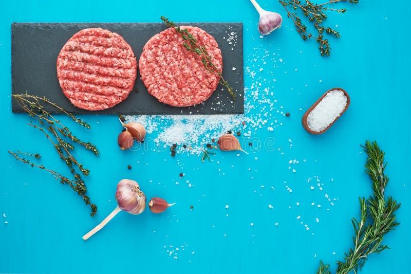 Carne cruda fresca de la carne de vaca con las hierbas y la sal en fondo de la turquesa foto de archivo libre de regalías