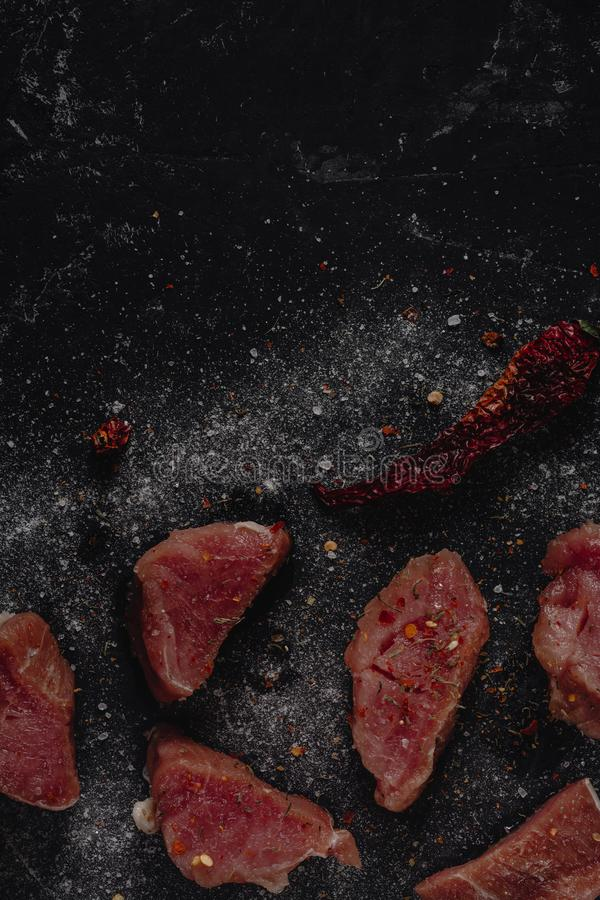 Carne cruda fresca de los medalions del cerdo con las especias, la sal y la pimienta en un fondo de piedra oscuro, espacio en bla imagenes de archivo