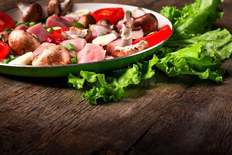 Carne cruda in piatto e padella, spezie, coltello sulla tavola di legno, fotografie stock