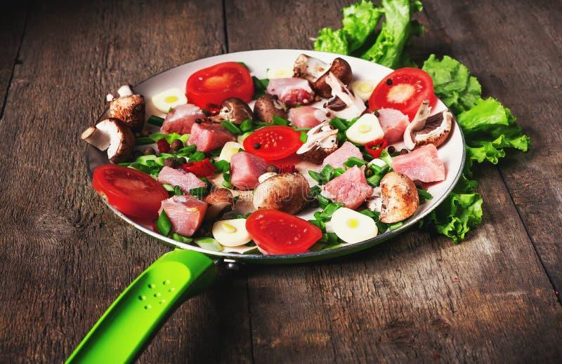 Carne cruda in piatto e padella, spezie, coltello sulla tavola di legno, fotografia stock