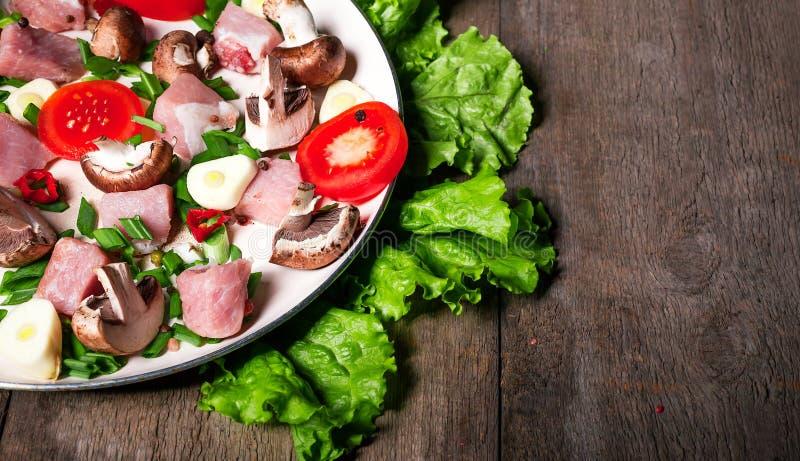 Carne cruda in piatto e padella, spezie, coltello sulla tavola di legno, fotografie stock libere da diritti