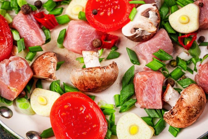 Carne cruda in piatto e padella, spezie, coltello sulla tavola di legno, immagine stock libera da diritti