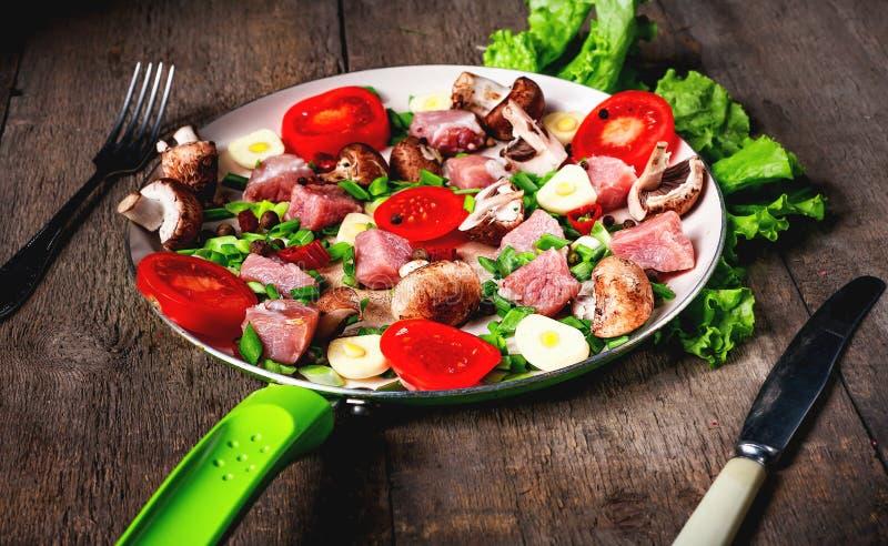 Carne cruda in piatto e padella, spezie, coltello sulla tavola di legno, fotografia stock libera da diritti