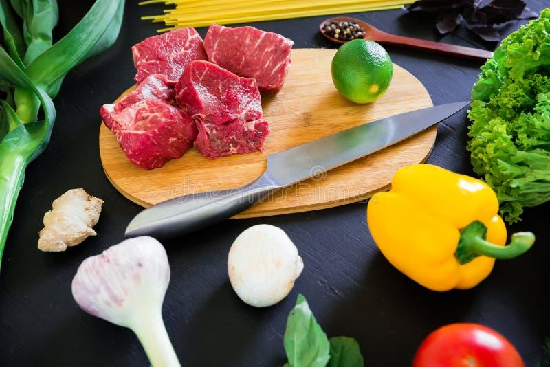 Carne cruda sul bordo, sul coltello, sulla pasta e sugli ortaggi freschi del cuoco sulla tavola scura Vista superiore Disposizion fotografia stock libera da diritti