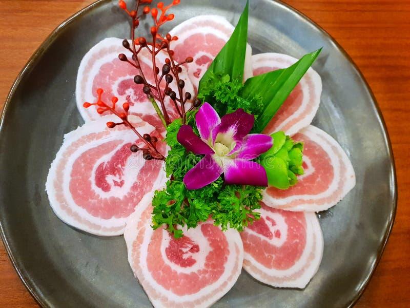 Carne cruda, vista superiore della pancia di carne di maiale affettata sulla banda nera sulla tavola di legno immagine stock
