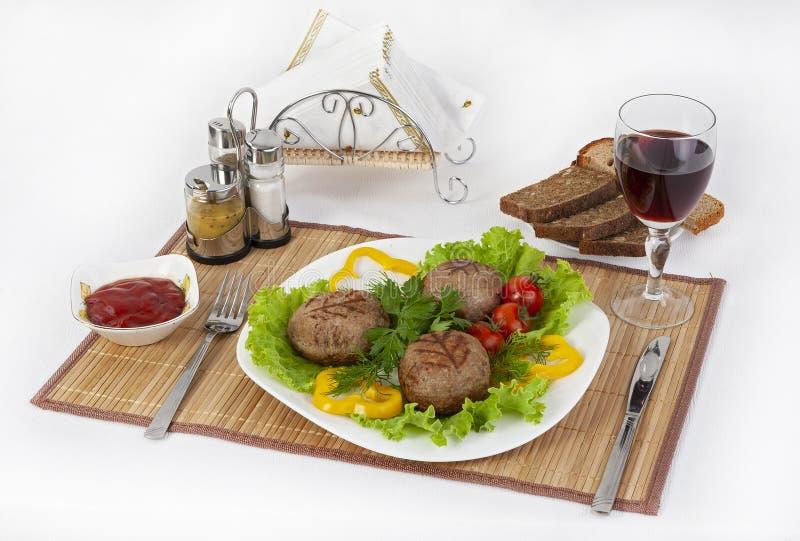 Carne da carne, rhizol redondo Costoletas redondas da carne com verdes, tomates e um vidro do vinho Café da manhã útil e saboroso foto de stock