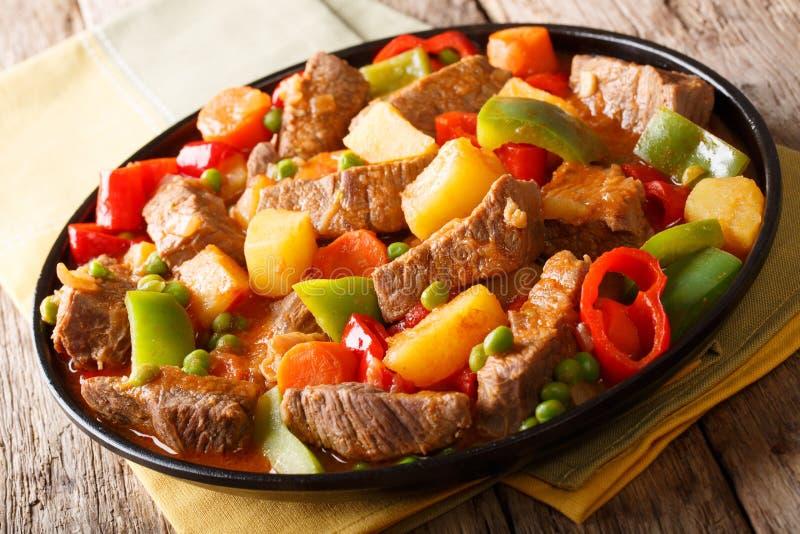 Carne de Caldereta com batatas, pimenta, ervilhas, tomates e cenouras foto de stock