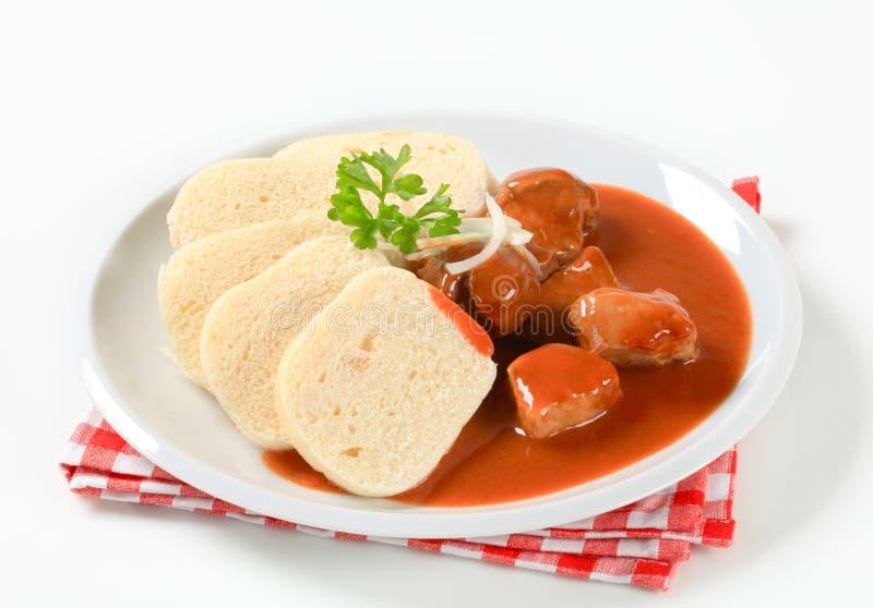Carne de carne de porco no molho de tomate com bolinhos de massa imagem de stock royalty free