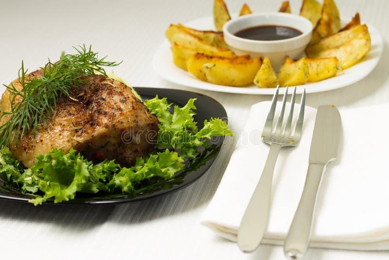 Carne de cerdo cocida servida con la patata asada a la parrilla imagen de archivo libre de regalías