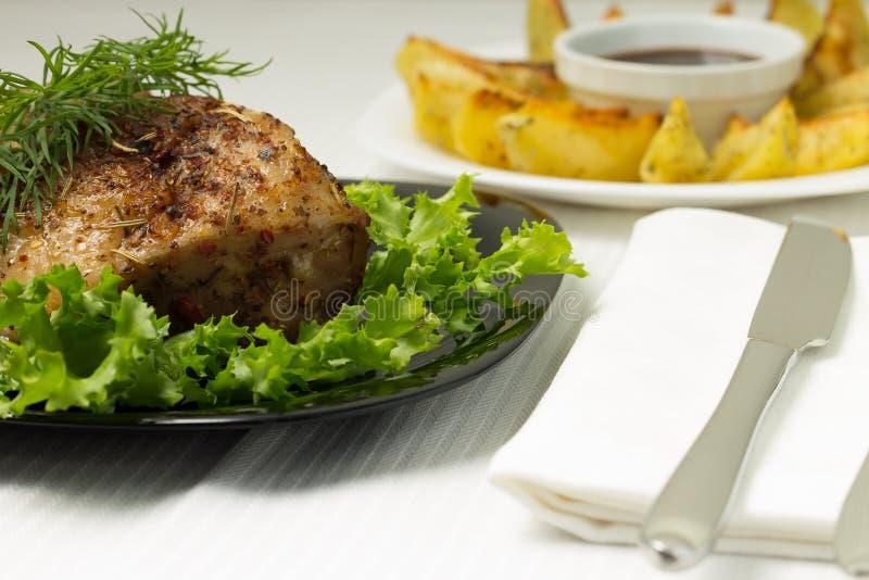 Carne de cerdo cocida servida con la patata asada a la parrilla foto de archivo