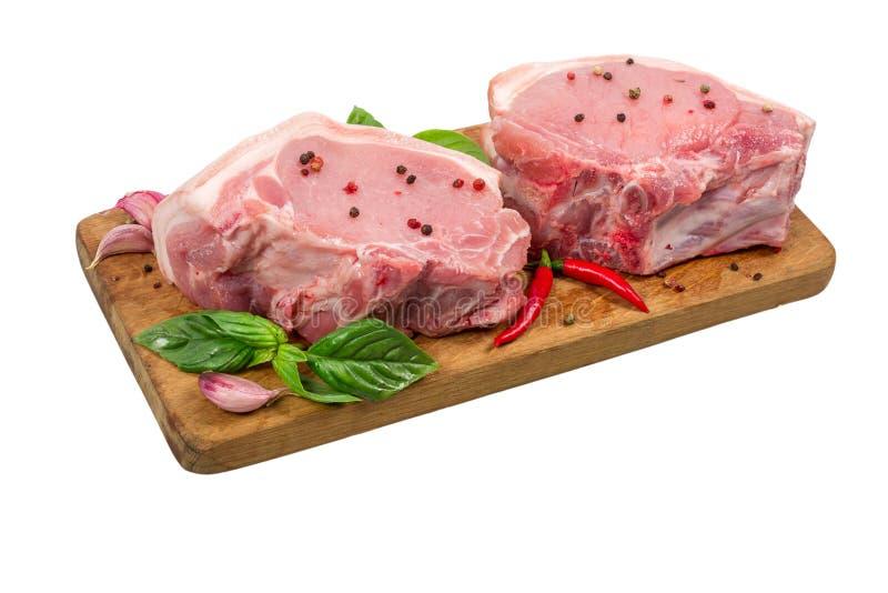 Carne de cerdo cruda en tabla de cortar de madera con las hierbas y las especias aisladas en el fondo blanco Cocinar concepto imagen de archivo
