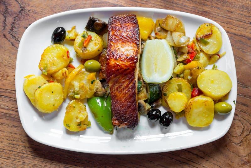 Carne de color salmón cocida con las patatas y las verduras en una placa blanca en un restaurante imagenes de archivo