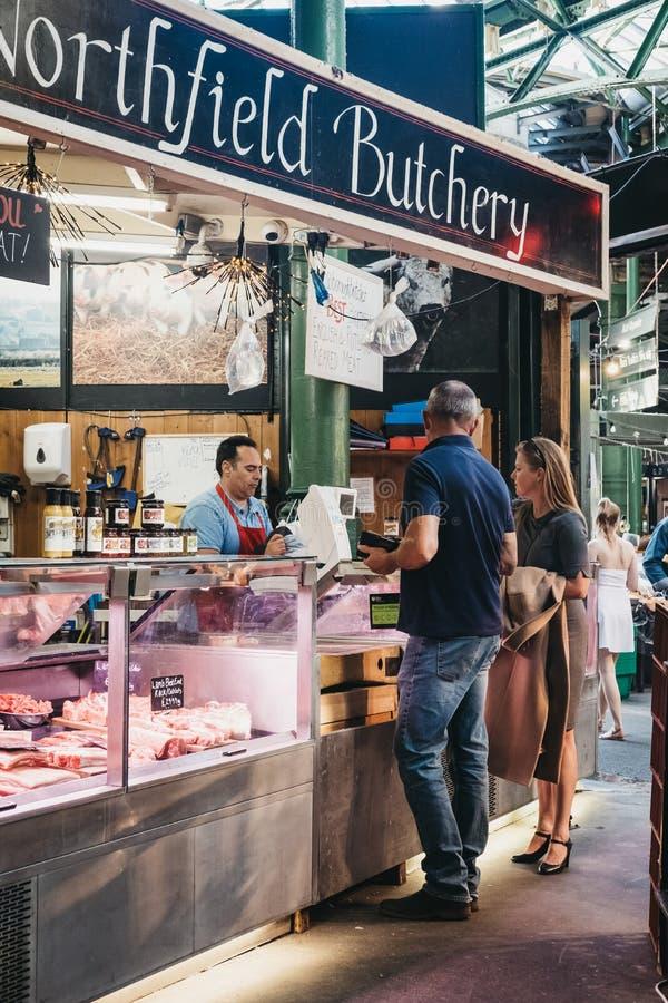 Carne de compra dos povos da loja do açougue de Northfield no mercado da cidade, Londres, Reino Unido imagem de stock royalty free