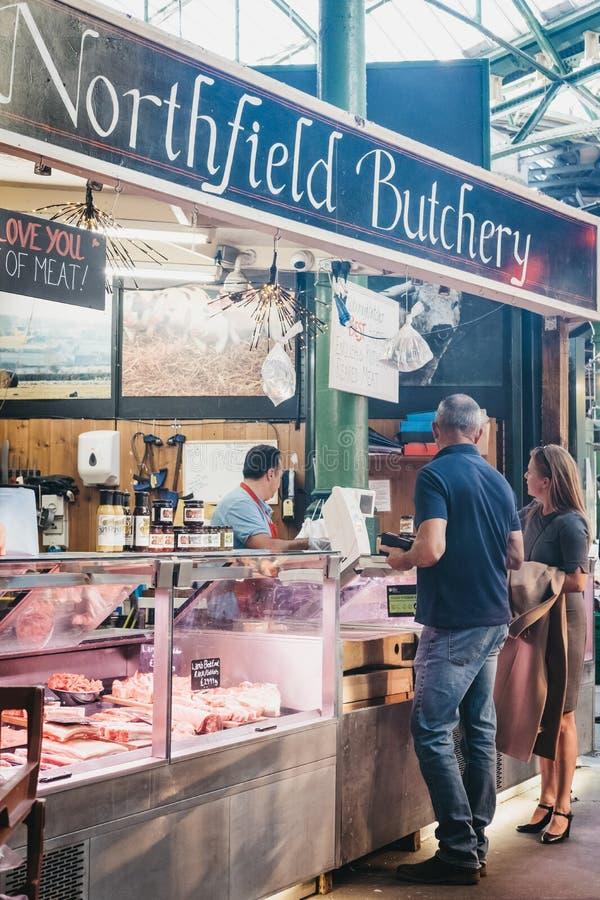Carne de compra dos povos da loja do açougue de Northfield no mercado da cidade, Londres, Reino Unido imagens de stock