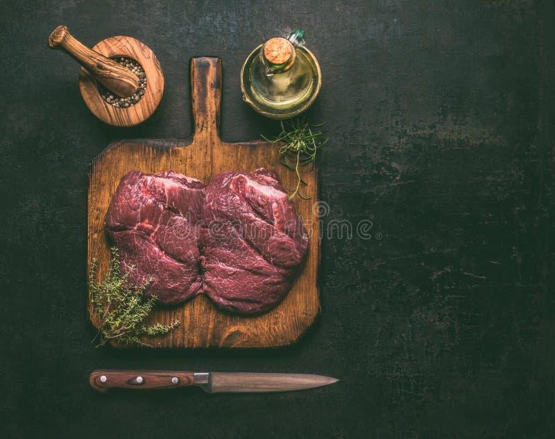 Carne de mármore crua da carne na placa de corte de madeira com ervas, especiarias, óleo e faca no fundo rústico escuro, vista su fotos de stock