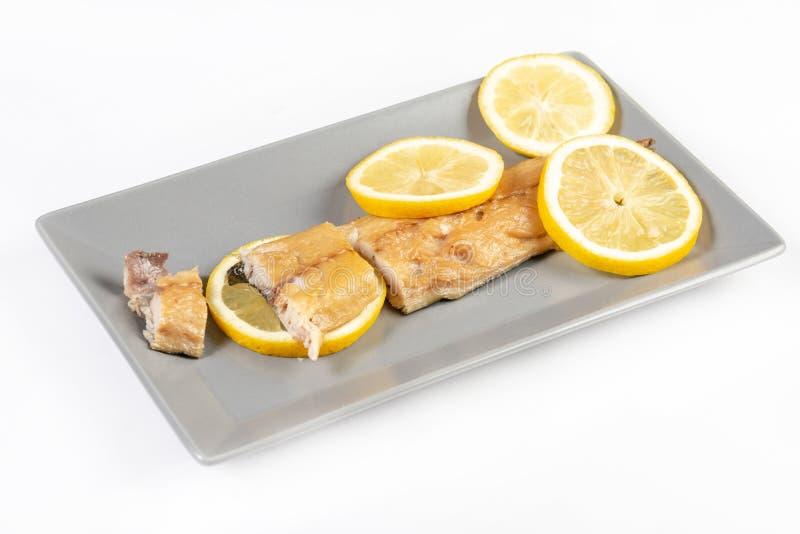 Carne de pescados secada de la caballa con los limones sobre el fondo blanco imagenes de archivo