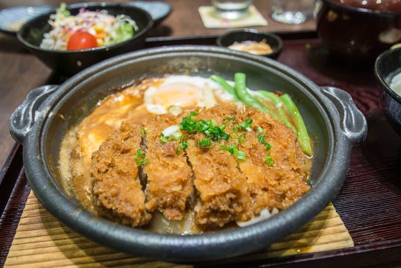 Carne de porco ateada fogo profunda fervida com parte superior fresca do ovo na bacia de arroz foto de stock