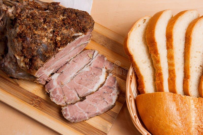 Carne de porco cozida com ervas e especiaria na placa de madeira e e nas fatias w imagem de stock
