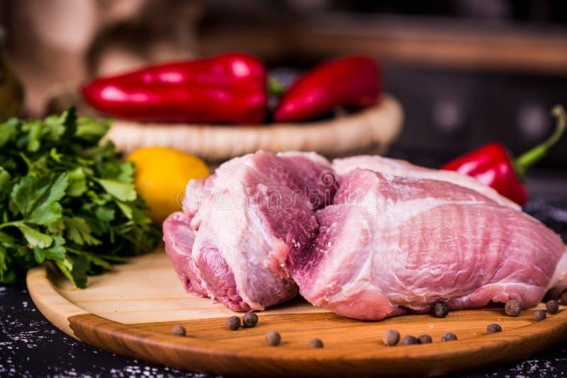 Carne de porco crua em uma placa de madeira imagens de stock