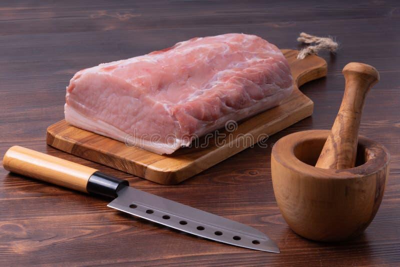 Carne de porco crua na placa de corte com almofariz de madeira e a faca japonesa imagem de stock