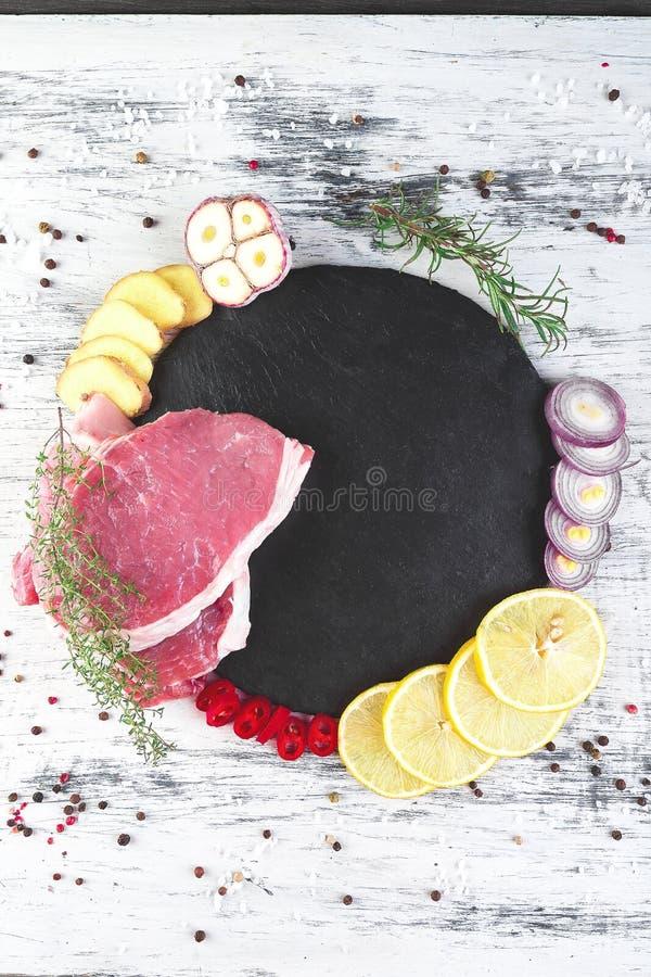 Carne de carne de porco crua na placa preta da ardósia com ingrediente da especiaria imagens de stock royalty free