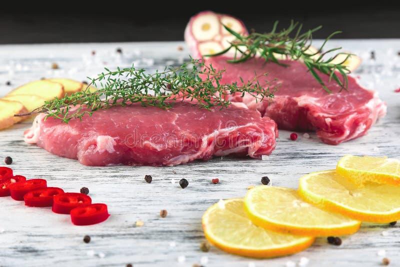 Carne de carne de porco crua na placa preta da ardósia com ingrediente da especiaria foto de stock royalty free