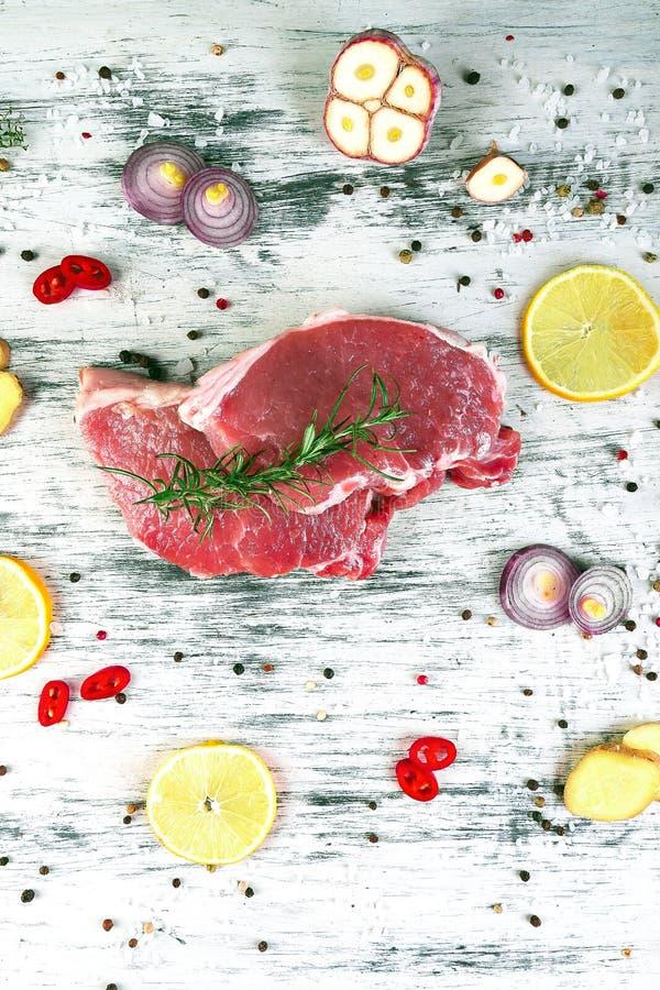 Carne de carne de porco crua na placa preta da ardósia com ingrediente da especiaria imagem de stock royalty free