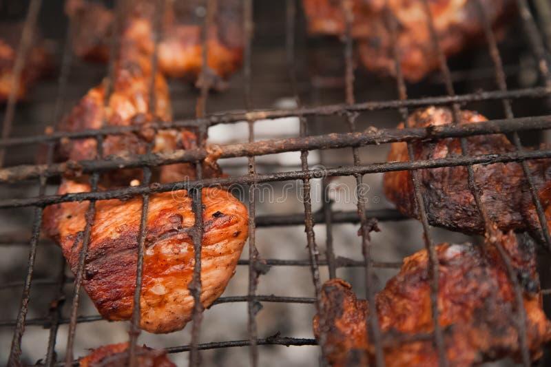 Carne de porco dos no espeto na grade com close-up do fumo Pedaços da carne do assado no fogo Quintal, conceito do resto, carne,  foto de stock