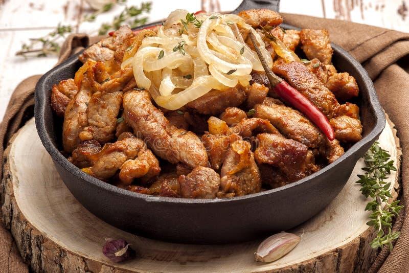 Carne de porco fritada com cebolas e pimento em uma bandeja do ferro fundido fotos de stock