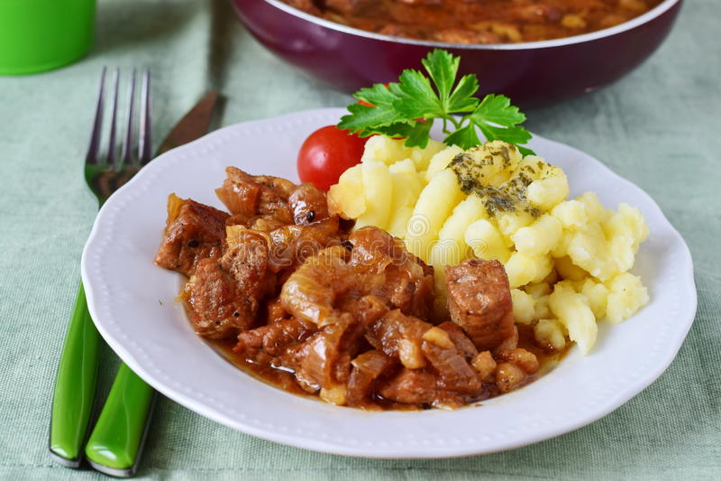 A carne de porco fritou com cebolas em uma placa com batata triturada Cozimento home fotos de stock