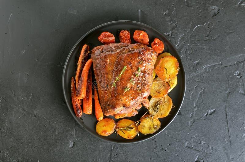 Carne de porco grelhada, batatas fritadas e cenouras fotografia de stock