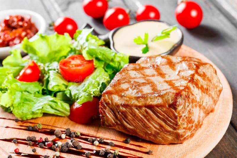 Carne de porco grelhada do bife com salada, tomates e molho do legume fresco na placa de corte de madeira imagem de stock royalty free