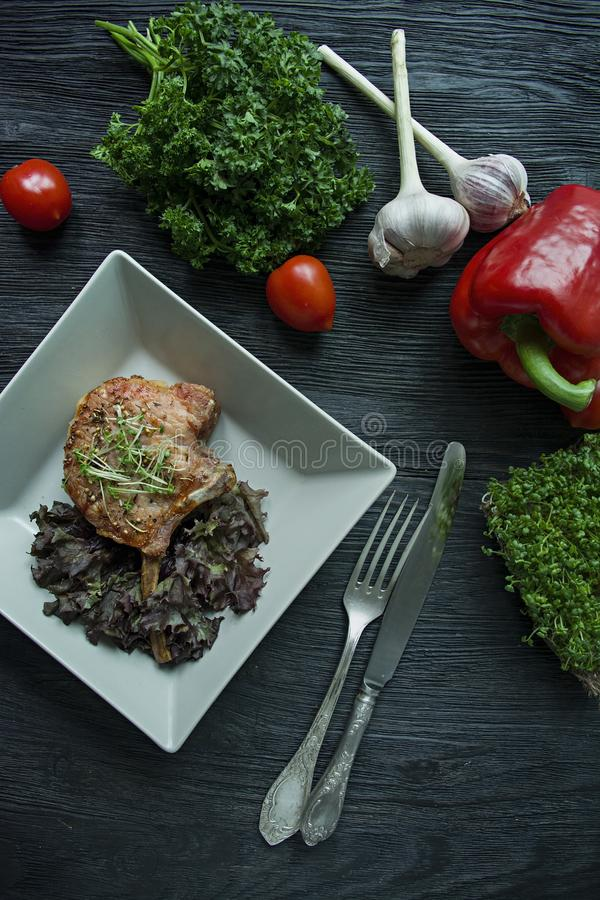 A carne de porco grelhada marca bifes com especiarias e ervas Decorou com pimento búlgaro fresco, tomates de cereja, alface, sals fotografia de stock