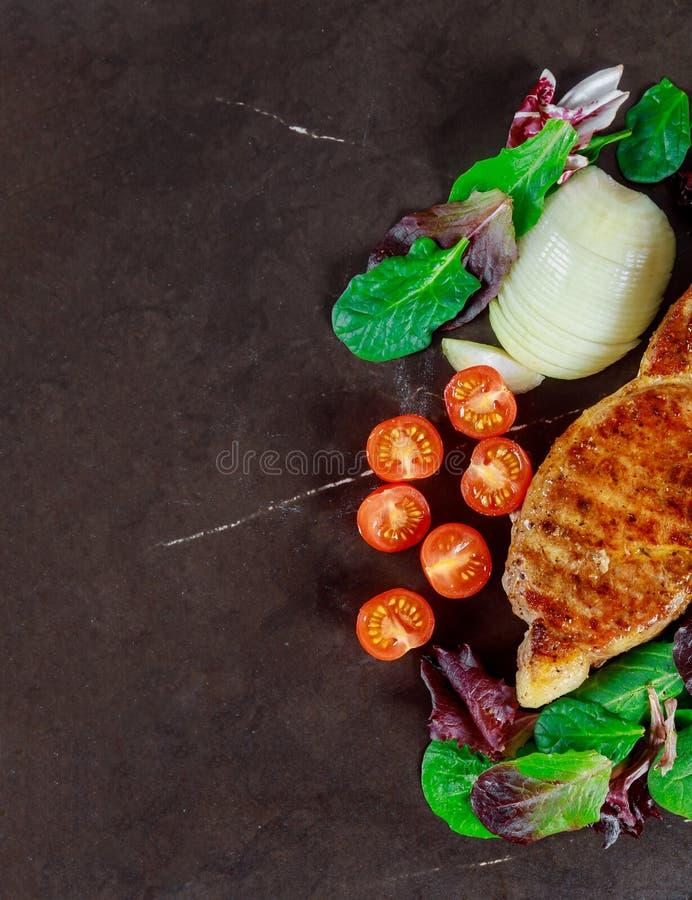Carne de porco grelhada rara suculenta do meio do bife com especiarias e egetables imagens de stock royalty free