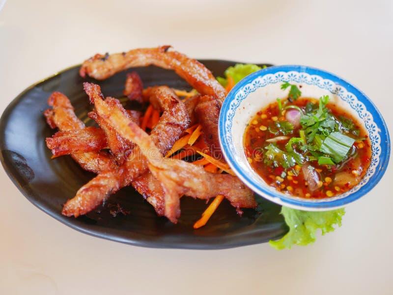 Carne de porco seca e frita e seca moo dad Deaw sendo colhida com seu molho picante saboroso ao lado imagem de stock