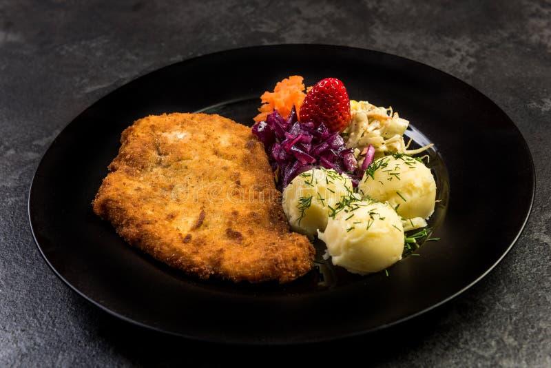 A carne de carne de porco serviu com batata e salada na placa imagens de stock royalty free