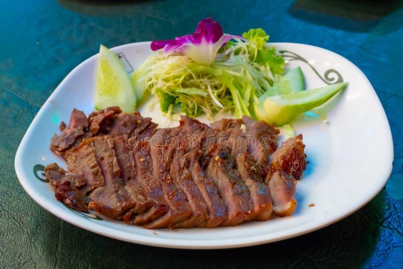 Carne de vaca asada a la parrilla en una placa blanca con la salsa y las verduras fotos de archivo
