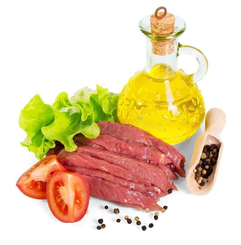 Carne de vaca, botella de aceite, verduras crudas y especias aisladas en blanco fotografía de archivo libre de regalías