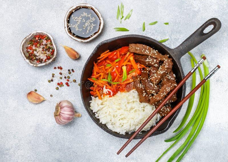 Carne de vaca con el arroz basmati y las verdura-zanahorias, paprikas, oni imagenes de archivo