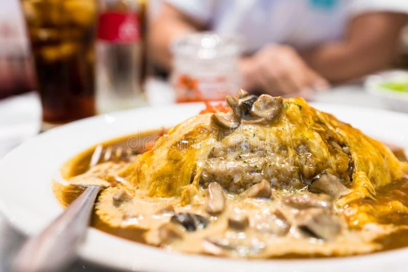 Carne de vaca del arroz y del curry envuelta en tortilla y rematada con una salsa de seta cremosa fotos de archivo