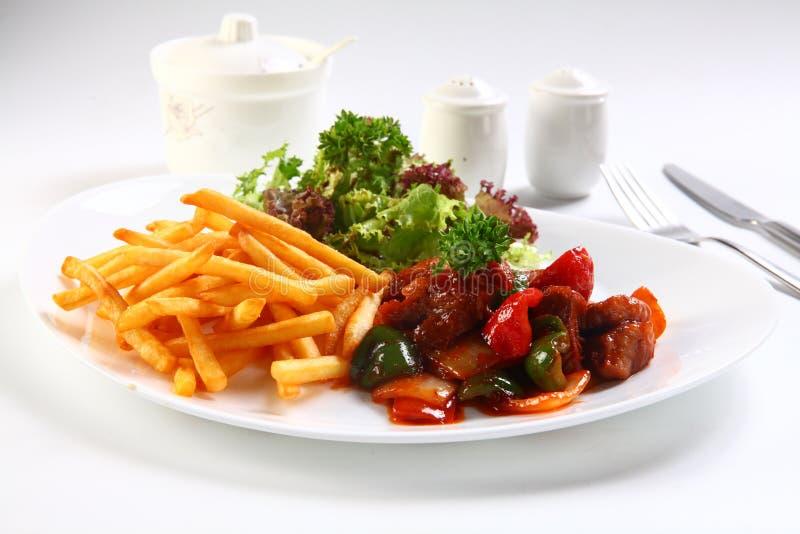 Carne de vaca frita con las patatas y la ensalada en la placa blanca en restaurante imagen de archivo libre de regalías