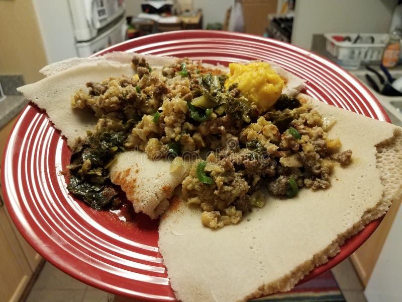 Carne de vaca de la comida etíope e intestino y pan picantes en la placa roja en cocina fotos de archivo