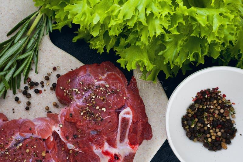 Carne de vaca, romero, pimienta en una tajadera de la piedra artificial foto de archivo