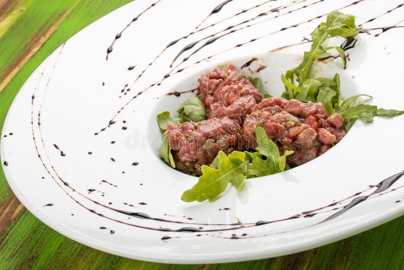 Carne de vaca tartare con las alcaparras en una tabla de madera verde imagen de archivo