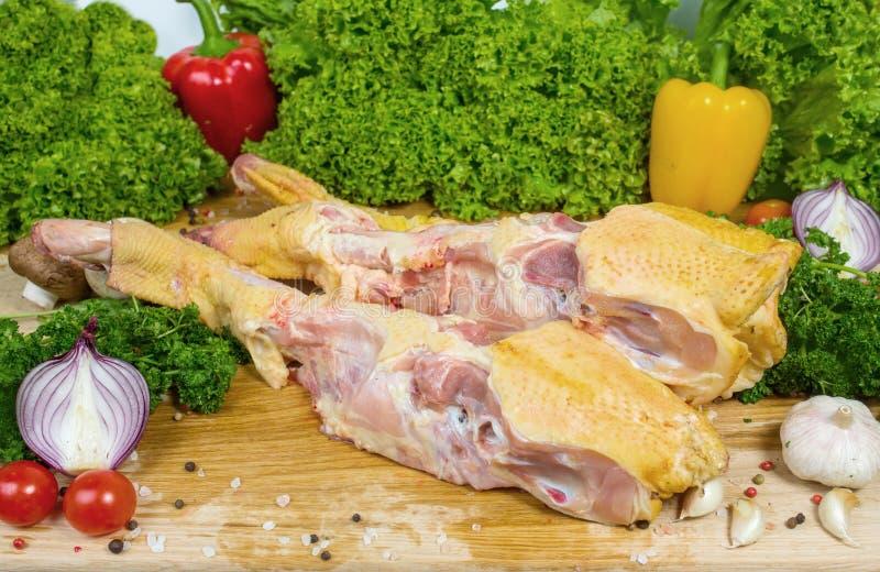 Carne del ganso, esqueleto del pato en una tabla de cortar de madera con los tomates de cereza, hojas de la lechuga, ajo, chile,  imágenes de archivo libres de regalías