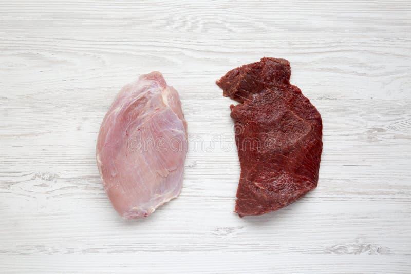 Carne del manzo e seno di tacchino crudi crudi su fondo di legno bianco, vista superiore Disposizione piana fotografie stock