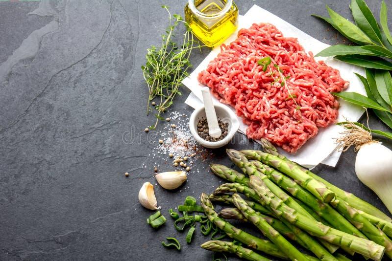 Carne del manzo ed ingredienti tritati - asparago, cipolla e spezie Triti ed erbe Carne tritata fotografia stock