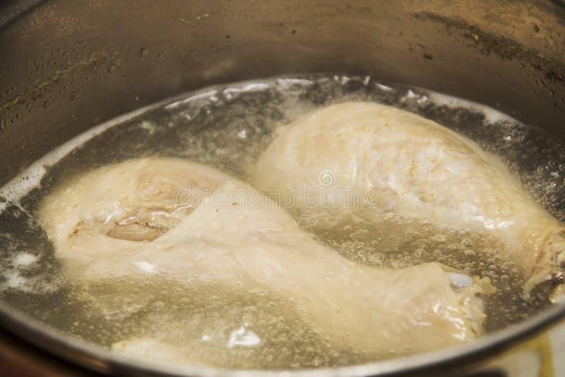 Carne del pollo en agua hirvienda en un cazo imágenes de archivo libres de regalías