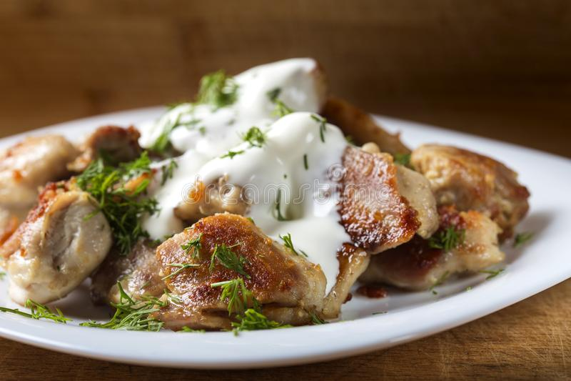Carne del pollo fritto con panna acida ed aneto sul piatto immagine stock